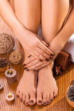 Brown manicure and pedicure on the bamboo Stock Photography