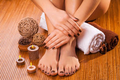 Brown manicure and pedicure on the bamboo Royalty Free Stock Photography