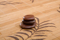 Brown massage stones composition on bamboo placemat Royalty Free Stock Photos