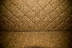 Brown material quilted upholstery background or texture. Closeup of couch quilted upholstery royalty free stock image