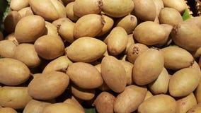 Brown matura gli zapodillas accatastati su sulle foglie verdi della banana fotografia stock libera da diritti