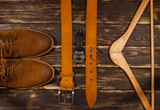 Brown men`s boots,  leather belt and hanger on wooden background. Stock Photos