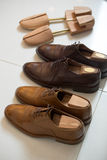 Brown men's shoes and shoe stratchers. Two pairs of brown handmade classic men's shoes  with a shoe pads and stretchers inside and beside the shoes Royalty Free Stock Image