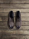 Brown men's shoes on a wooden background Royalty Free Stock Image