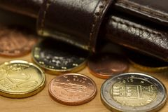 Brown men`s wallet and euro coins on wooden table. Stock Image