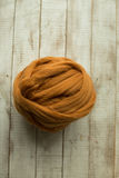 Brown merino wool ball. On wooden background royalty free stock image