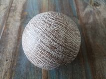 Brown metal ball on brown wooden table. Brown metal ball or sphere on brown wooden table stock image