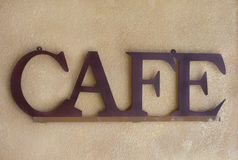 Brown Metal Cafe Sign against a Textured Wall. Horizontal image of a brown metal sign spelling out the word cafe against a brown textured wall Royalty Free Stock Image