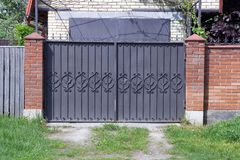Brown metal gate with forged pattern and part of a brick fence outside stock photo