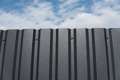Brown Metal Plate Against Blue Cloudy Sky. Siding. Seamless Surface Of Galvanized Steel. Industrial Building Wall Made Stock Photos