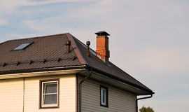 Brown metal roof. Of a house with a red brick pipe stock photography