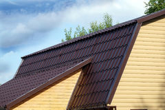 Brown metal roof of rural house covered with yellow siding over blue sky with clouds on sunny day Stock Photos