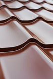 Brown metal roof tiles. Closeup of brown metal tiles, roof sheathing Royalty Free Stock Photography