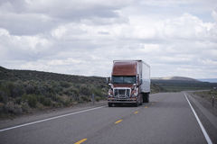 Brown modern semi truck with trailer driving long Nevada highway. Pro Semi Truck with a protective aluminum bumper guard and trailer carries commercial cargo on Stock Photo