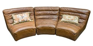Brown modular leather semi-circular sofa with tapestry cushion isolated white background.  stock image
