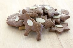 Brown moravian dark gingerbreads with sliced almonds on wooden table, christmas cookies stock photo