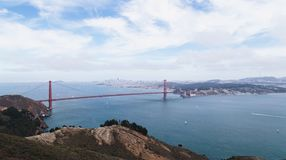 Brown Mountain and Red Steel Bridge in Body of Water during Daytime Royalty Free Stock Images