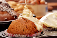 Brown muffin in the mold with white icing Stock Photography