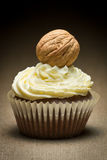 Brown muffin with vanilla cream and big walnut stock photography