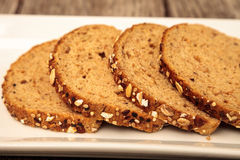 Brown multigrain bread slices on a white plate. Brown multigrain bread slices placed in a row on a white plate Stock Images