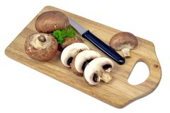 Brown mushrooms on wooden board Stock Images
