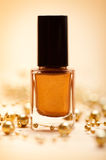 Brown nail polish. And golden pearls Royalty Free Stock Photo