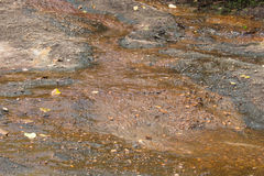 Brown natural wet rocks in river water background Stock Images