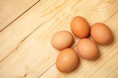 Brown nicely lit eggs located in groups on wooden background Stock Image