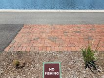 Brown no fishing sign with red bricks and water and asphalt. Brown no fishing sign with red bricks and river or stream and asphalt royalty free stock photography