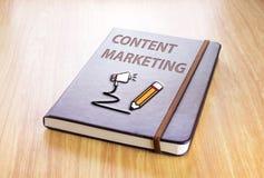 Brown notatnik z Zadowolonym marketingu słowem i ołówek z mówimy Zdjęcia Royalty Free