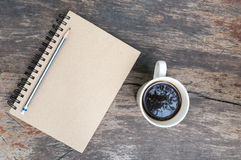 Brown note book with coffee cup. On grunge wood Royalty Free Stock Images