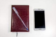 Brown note with pen and phone on the table Stock Photography