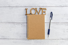 Brown notebook and blue pen o Royalty Free Stock Photo