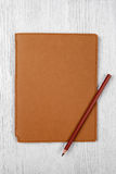 Brown notebook and a pencil on white wooden table, top view Stock Photos