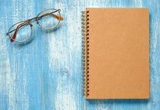 Brown-Notizbuch mit Gläsern auf blauem hölzernem Lizenzfreies Stockbild