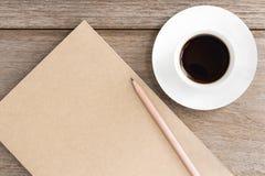 Brown-Notizbuch mit Kaffeetasse auf hölzernem Hintergrund Stockbild