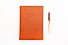 Brown-Notizbuch und -stift lokalisiert auf dem Weiß Lizenzfreie Stockfotos