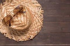 Brown okulary przeciwsłoneczni i kapelusz jesteśmy na drewnianym tle Obrazy Stock