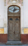 Brown old door with stucco. Brown old door on background of ancient house with stucco Stock Image