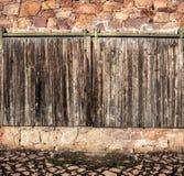 Brown old  gates on masonry wall Royalty Free Stock Photos