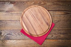 Brown old vintage wooden table with framed red tablecloth napkin and pizza cutting board.Thanksgiving day and Cristmas table royalty free stock photography
