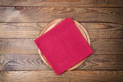 Brown old vintage wooden table with framed red tablecloth napkin and pizza cutting board.Thanksgiving day and Cristmas table royalty free stock photo