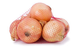 Brown onion in packed in a bag. Brown onion in packed in a red net bag Royalty Free Stock Photos