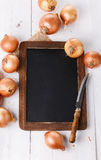 Brown onion on a white wooden background Royalty Free Stock Photos