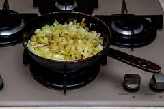 Brown onions fried in a pan stock images