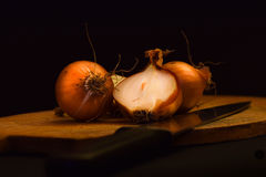 Brown onions on a wooden cutting board royalty free stock images