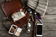Brown open bag with various female accessories. Knitted hat, smart phone, dollars, flat lay on wooden boards Stock Photo