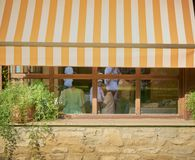 Brown orange and white awning covering a window in a restaurant while unidentified people are inside. Protection, sunny, sunshade, outdoors, canvas, day, house royalty free stock images