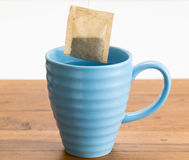 Brown organic green tea bag lowered in mug Stock Photos