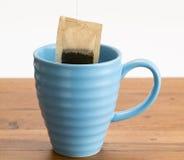 Brown organic green tea bag lowered in mug. Organic green tea or herbal tea being lowered into a blue mug on wooden table Royalty Free Stock Image